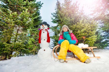 neve palle: Ragazza che si siede sulla slitta con il pupazzo di neve e palle di neve nella foresta di inverno