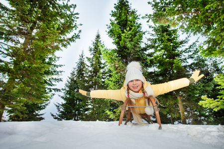on the skids: Happy girl enjoying a sledge ride in the forest at the sunny day Stock Photo