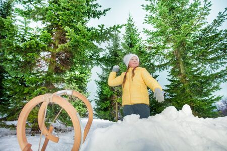 skids: Girl playing snowball on the fir background at the sunny day Stock Photo