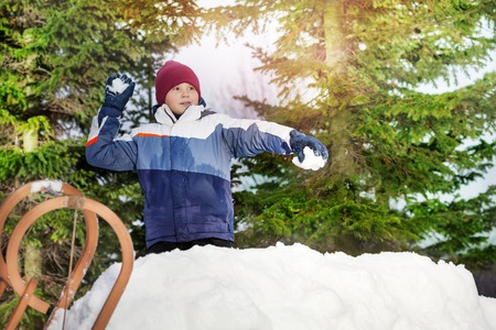 palle di neve: Boy throwing snowballs in his winter wear on the green spruces background