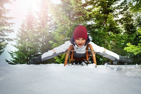 sledging: Funny kid boy sledging at winter time in the forest Stock Photo