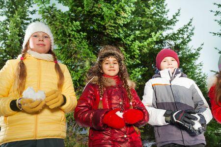 palle di neve: Ragazzo e ragazze in piedi con le palle di neve in mano si prepara a giocare i giochi invernali