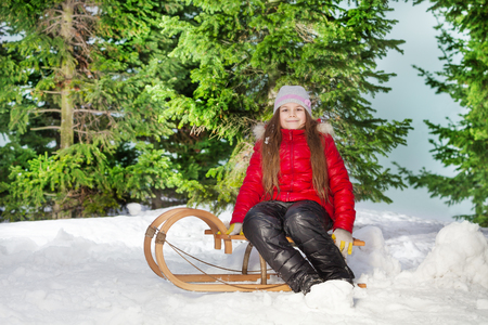skids: Smiling beautiful long-haired  girl sitting on wooden sledge in the winter forest
