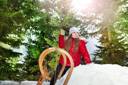 skids: Beautiful girl plays in the snow with a snowball at the forest Stock Photo