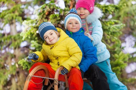 skids: Close portrait of three happy little kids on sledge in the park slide down on snow hill Stock Photo