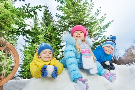 palle di neve: Kids boys and girls in colorful coats behind snow fortress wall throw snowballs