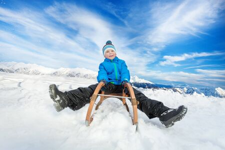 on the skids: Little boy in blue coat slide on sledge from the hill with legs first