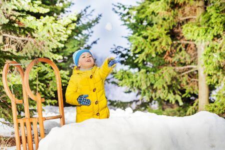 boule de neige: Petit gar�on Jet� boule de neige debout derri�re faite par les enfants Snowball Banque d'images