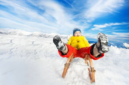 skids: Little boy slide on sledge from the hill with legs first Stock Photo