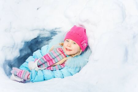 kids wear: Little girl play in snow smiling to the camera on winter day