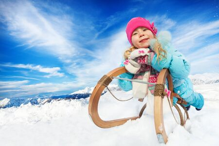 skids: Nice little girl in pink hat and blue coat lay on sledge on sunny winter day outside