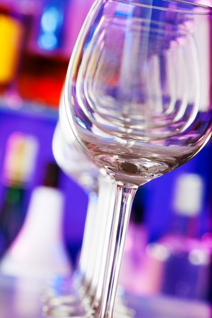 winy: Sill life photograph of the wine glasses standing in a row in a bar with bottles on background