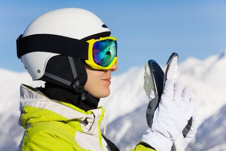 ski mask: Close portrait of woman in ski mask and helmet standing over the mountains