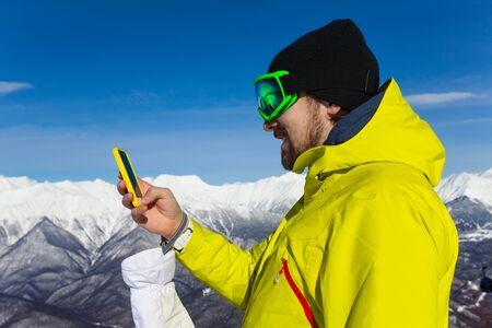 ski mask: Man skier with beard and ski mask text holding phone standing on top of the mountain Stock Photo