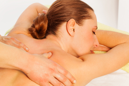 rubdown: Portrait of relaxed woman in spa salon getting massage at the couch Stock Photo