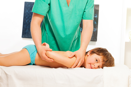 rubdown: Little boy lying at the massage couch at the light rehabilitation cabinet Stock Photo