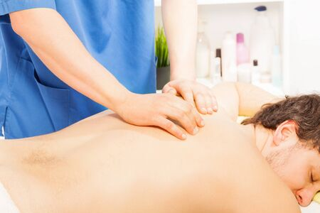 rubdown: Young man relaxing in spa massage salon laying on the massage table Stock Photo