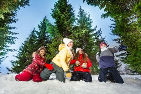 competes: Four kids competes in throwing snowballs, winter games, at snowy winter wood against high spruces