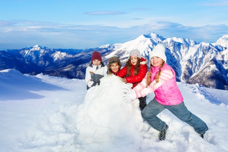 rolling up: Four happy friends rolling up big snowball against beautiful snow mountains peaks Stock Photo
