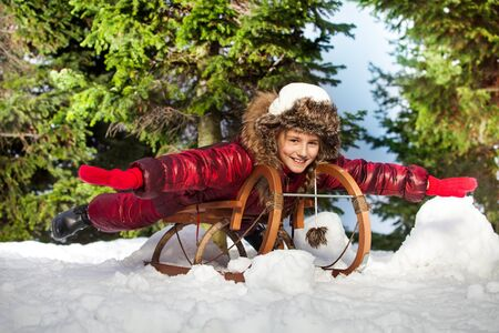 skids: Cute funny girl in colorful winter clothes having fun on wooden snow sledge at the forest