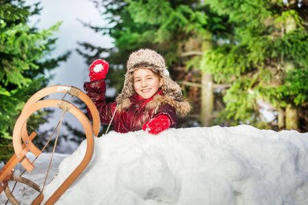 skids: Smiling girl throwing snowball from the snow tower at the sunny winter day