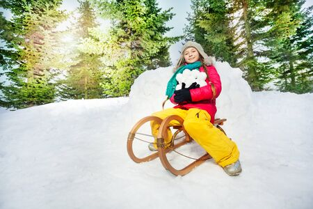 skids: Girl sitting on the wooden sledge and holding snowballs at the sunny winter day