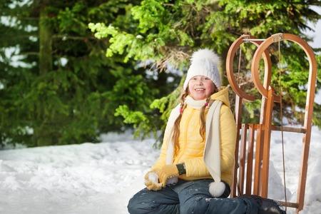 skids: Smiling girl sitting on snow near her wooden sledge