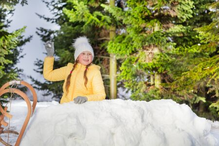 skids: Happy girl throwing snowball from the snow tower in the forest