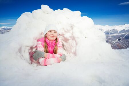 igloo: Happy girl in pink clothes laying at the snow hole against beautiful mountains