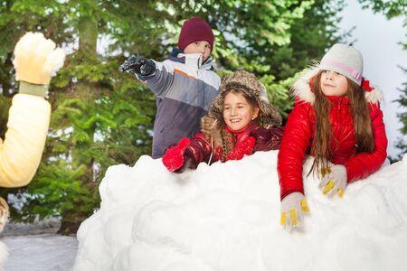 palle di neve: Un ragazzo e due ragazze lanciando palle di neve che si nascondono dopo torre di neve nella foresta d'inverno Archivio Fotografico