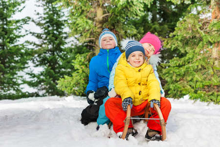 on the skids: Group of boys and girls slide on sledge in the park on winter day