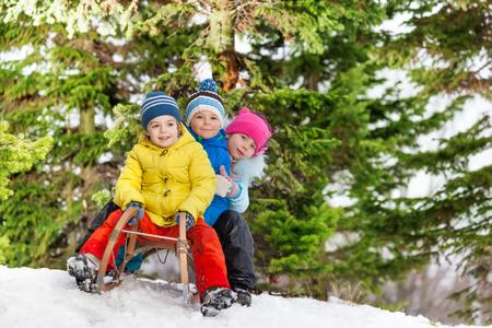 skids: Group of kids boys and girls slide down on sledges in the winter park
