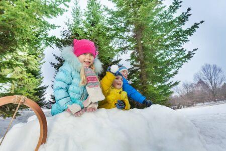 snowballs: Kids boys and girls behind snow fortress wall throw snowballs