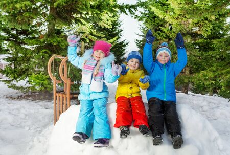 lift hands: Children boys and girls sit on snow fortress wall and lift hands up Stock Photo