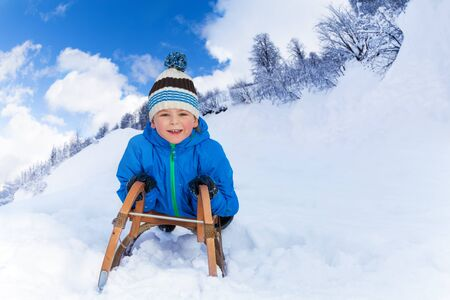 skids: Little boy lay on the sledge and slide down front view