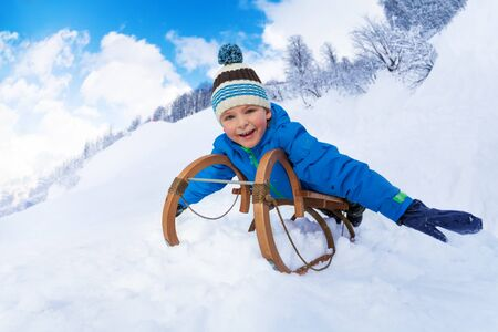 skids: Little boy slide down on sledge smiling and looking at camera stretching hands Stock Photo