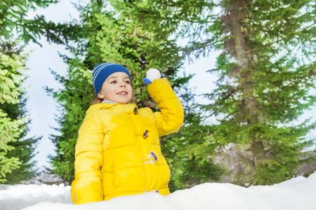 3 5 years: Little boy with snowball play outside on winter day among trees in yellow coat