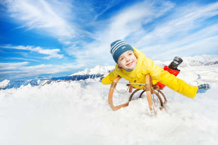 skids: Little boy in yellow coat on sledge and stretched hands in the mountain Stock Photo