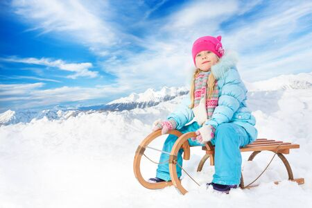 skids: Little girl in blue on sledge in the mountains sit and look at the camera Stock Photo