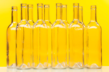 ten empty: Ten empty glass transparent bottles standing in a row against yellow background Stock Photo