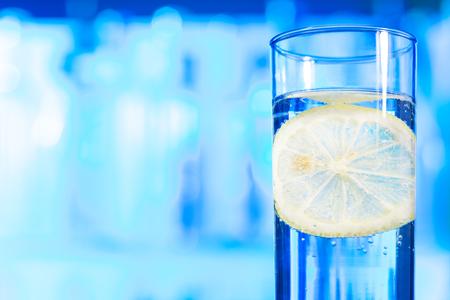 vaso con agua: Foto de primer plano de vidrio soluble brillante con rodaja de limón en el interior