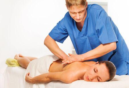 Masseur doing massage on beautiful woman body in the spa salon