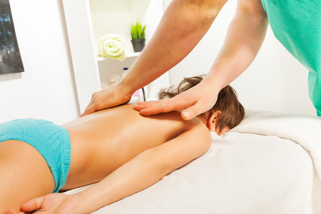 rubdown: Little boy relaxing with the massage on couch in the spa salon Stock Photo