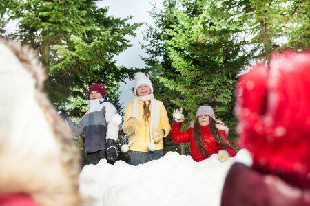 palle di neve: Amici felici, ragazze e ragazzo a giocare a palle di neve che si nascondono dietro la torre neve nella foresta d'inverno