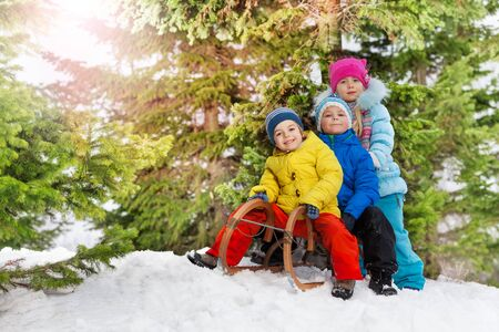 skids: Three happy little kids on sledge in the park slide down on snow hill