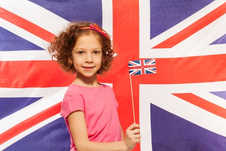 british girl: Beautiful curly-haired girl with flag at her hand in front of British flag