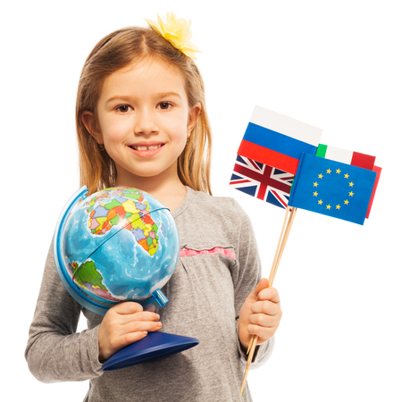 Smiling schoolgirl holding a globe and flags of European nations in her hands, isolated on white