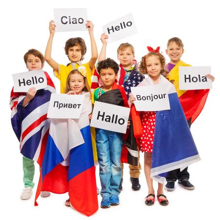 Grupa siedmiu szczęśliwych dzieci owinięte w flagi USA i krajów europejskich, pozdrowienia wzajemnie w różnych językach, na białym tle Zdjęcie Seryjne