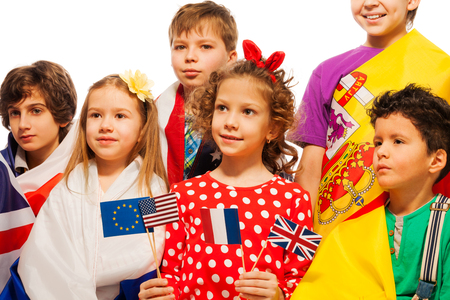 foreign country: Portrait of six children wrapped in flags of USA and European nations holding pennons of EU, USA, France and UK, isolated on white