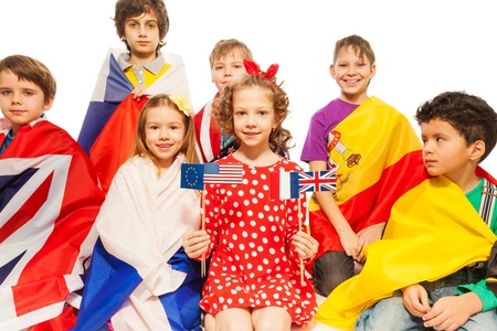 foreign national: Children sitting with flags wrapped in flags of USA and European nations, isolated on white background